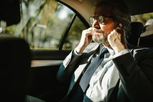 An older businessman putting on headphones prepares for a conference call.