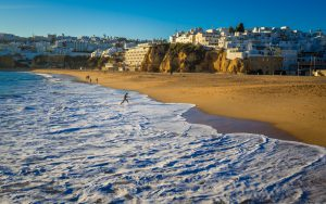 Winter light in Portugal at Albufeira's sandy beach in Portugal. City view from the beach. Waves.